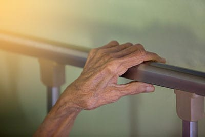 Hand of old woman on bed rail