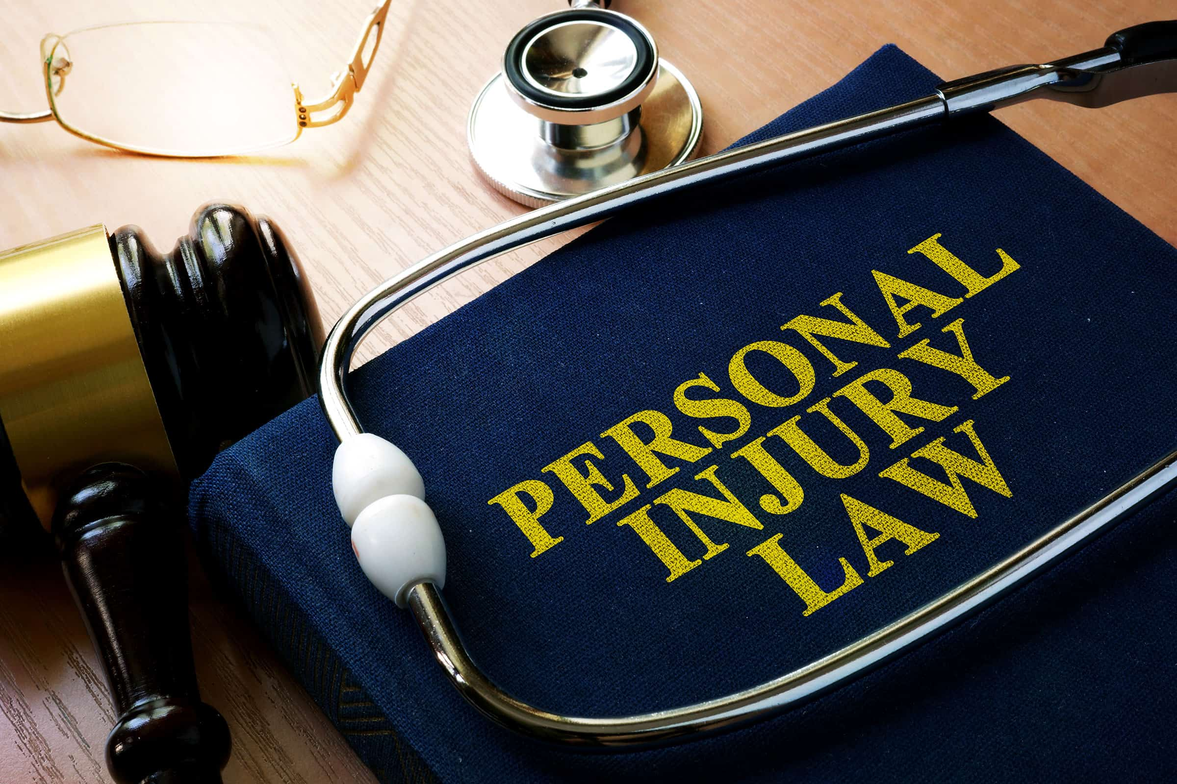 Personal injury law book, gavel and stethoscope