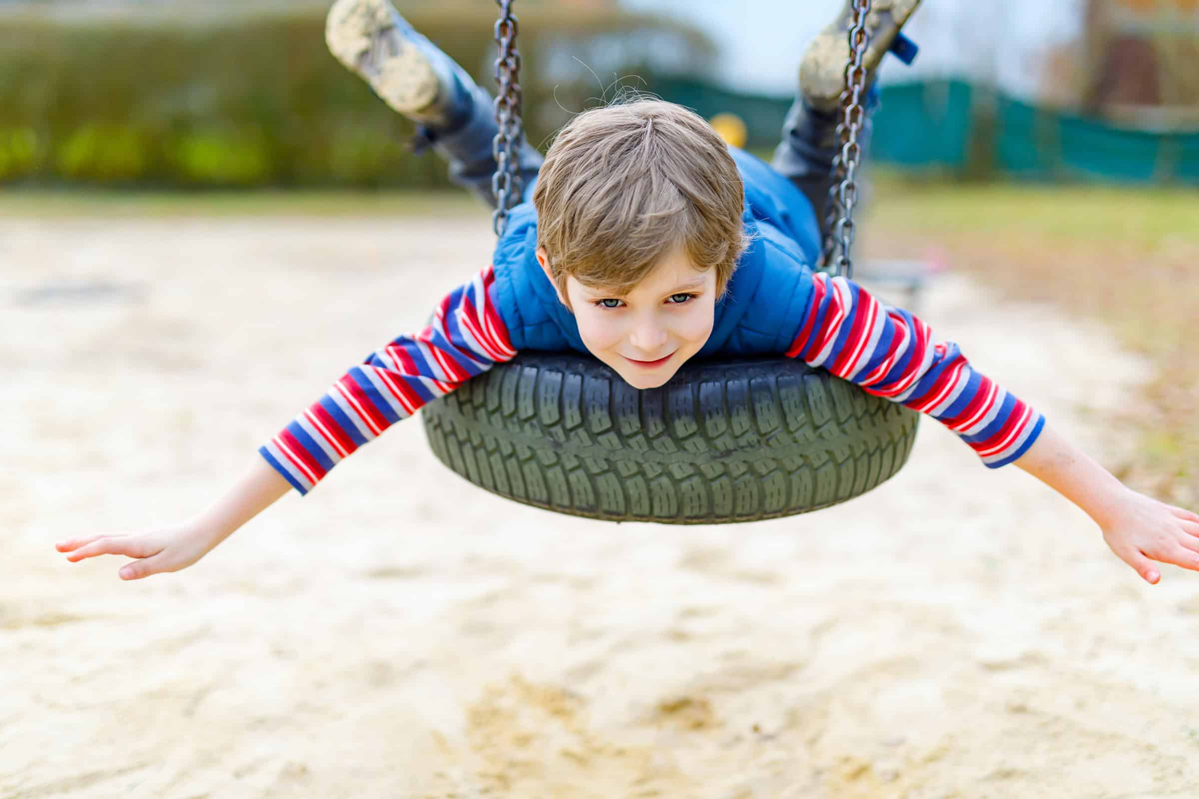 Child on belly on tire swing on playground