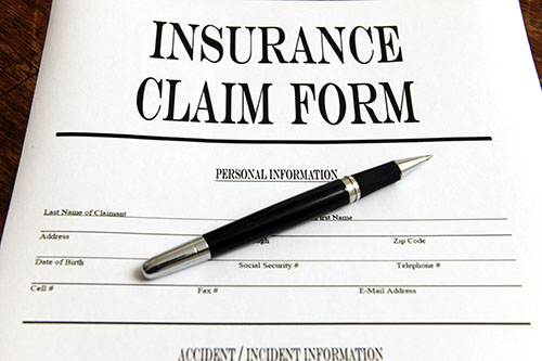 Graphic of an insurance claim form for auto accidents with a pen laying on top of it