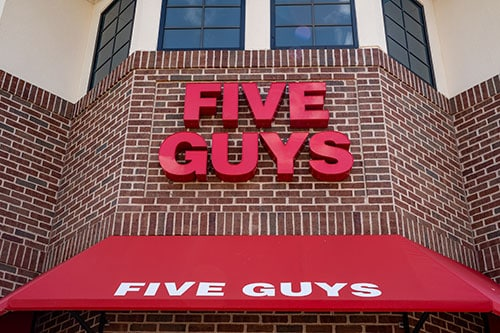 five guys sign on brick building