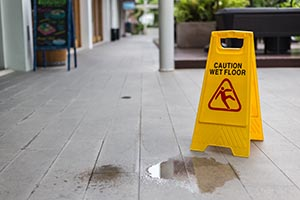 Yellow Wet Floor Sign in Front of Liquid on Floor