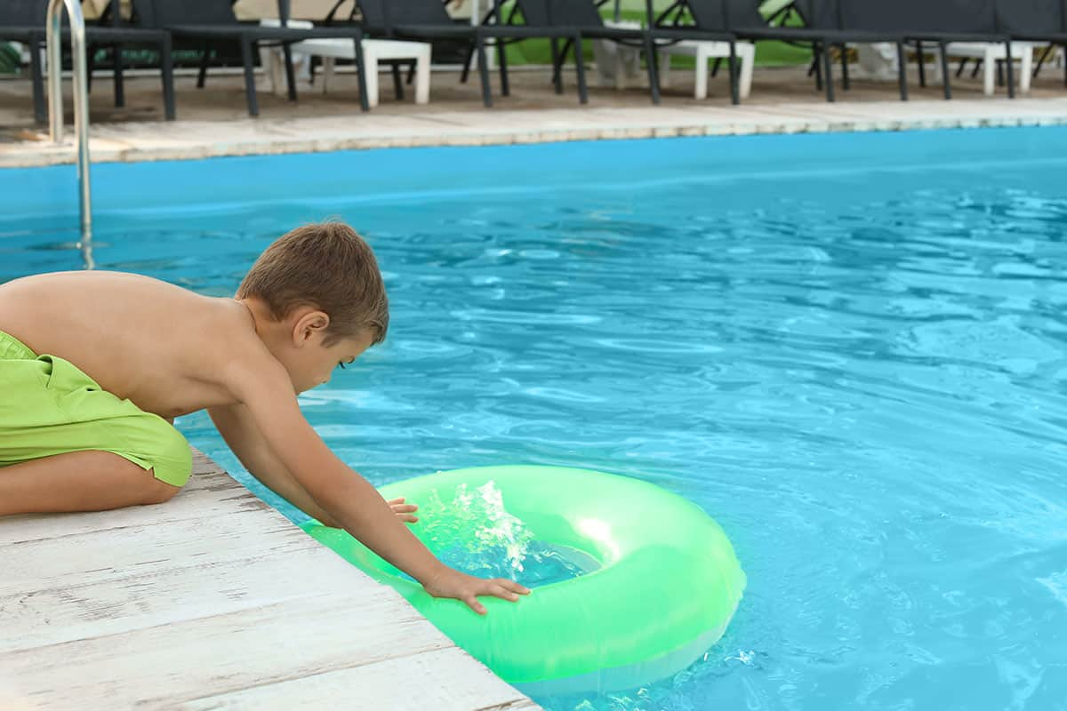 Little child on swimming pool deck reaching for inflatable tube in the pool