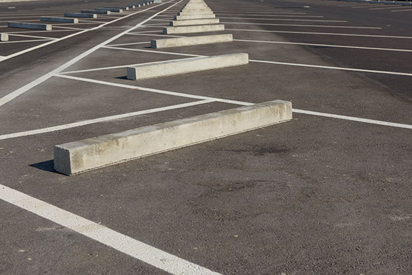 Rows of car parking blocks precisely aligned in a parking light